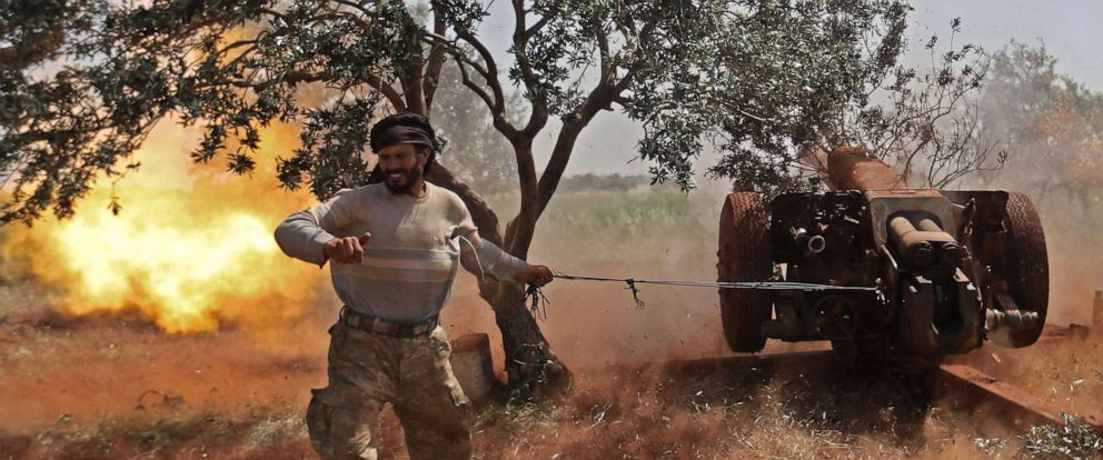 PHOTO: A Syrian fighter from the Turkish-backed National Liberation Front (NLF) fires a heavy artillery gun from the rebel-held Idlib province against against regime positions in the northern part of Hama province, May 22, 2019.