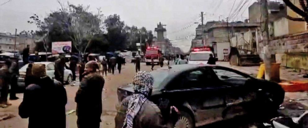 PHOTO: An image grab taken from a video published by Hawar News Agency (ANHA) on January 16, 2019, shows people gathered at the scene of a suicide attack in the northern Syrian town of Manbij.