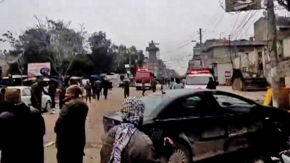 An image grab taken from a video published by Hawar News Agency (ANHA) on January 16, 2019, shows people gathered at the scene of a suicide attack in the northern Syrian town of Manbij.