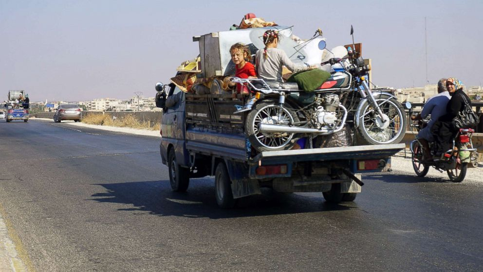 Syrian children riding in the back of a loaded truck drive along the main Damascus-Aleppo highway near the town of Saraqib in Syria's mostly rebel-held northern Idlib province, as families flee from the countrysides of Hama and Idlib provinces.
