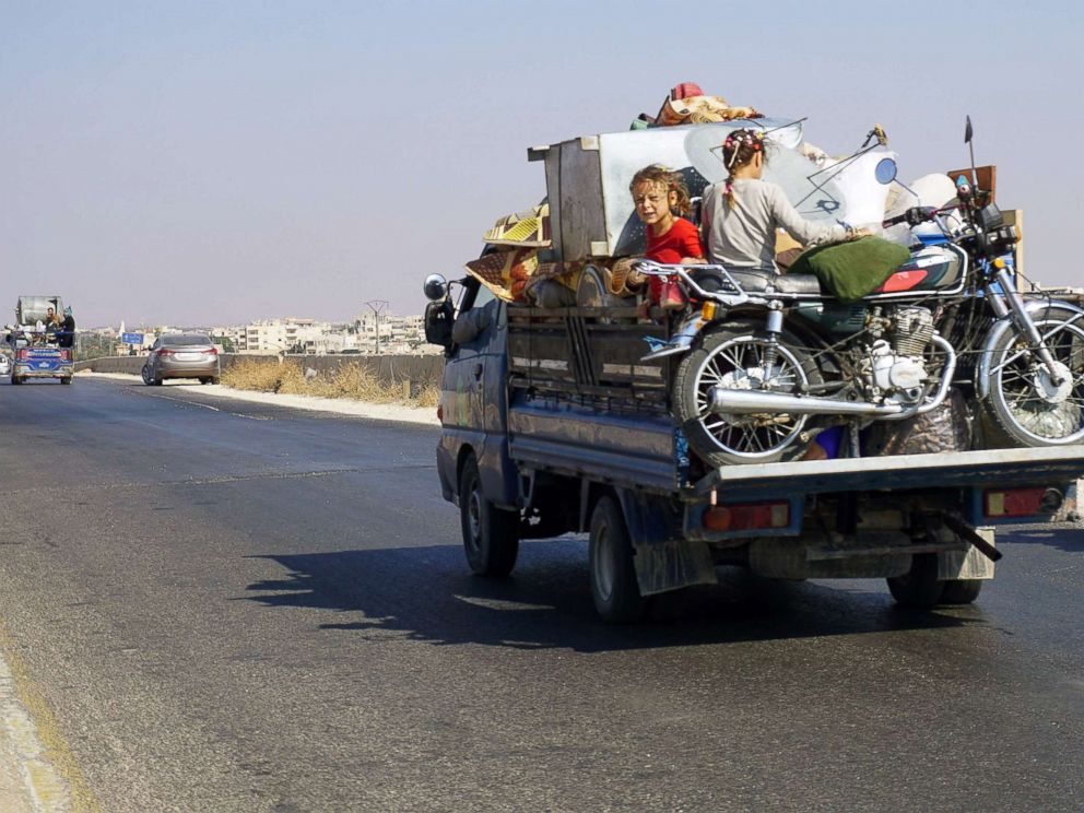 PHOTO: Syrian children riding in the back of a loaded truck drive along the main Damascus-Aleppo highway near the town of Saraqib in Syrias mostly rebel-held northern Idlib province, as families flee the countrysides of Hama and Idlib provinces.
