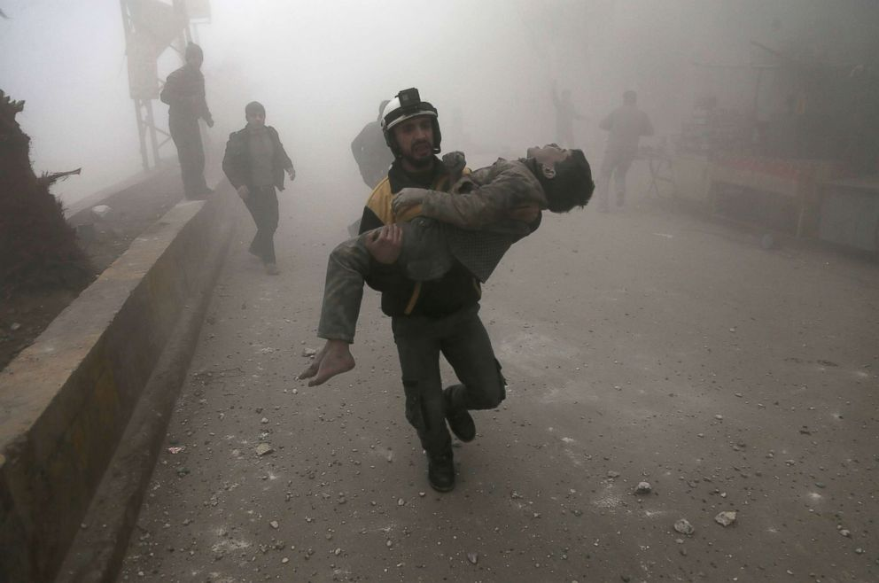 A volunteer from the Syrian Civil Defence, known as the White Helmets, carries a wounded boy after digging him out of the rubble following an air strike in the besieged rebel-held Eastern Ghouta area near Damascus, Syria, Jan. 9, 2018.