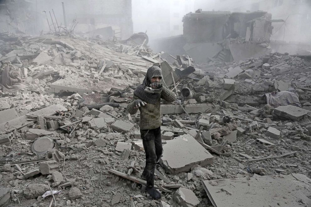 PHOTO: A girl appears from the rubble holding her shoe following an air strike in the besieged rebel-held Eastern Ghouta area near Damascus, Syria, Jan. 9, 2018.