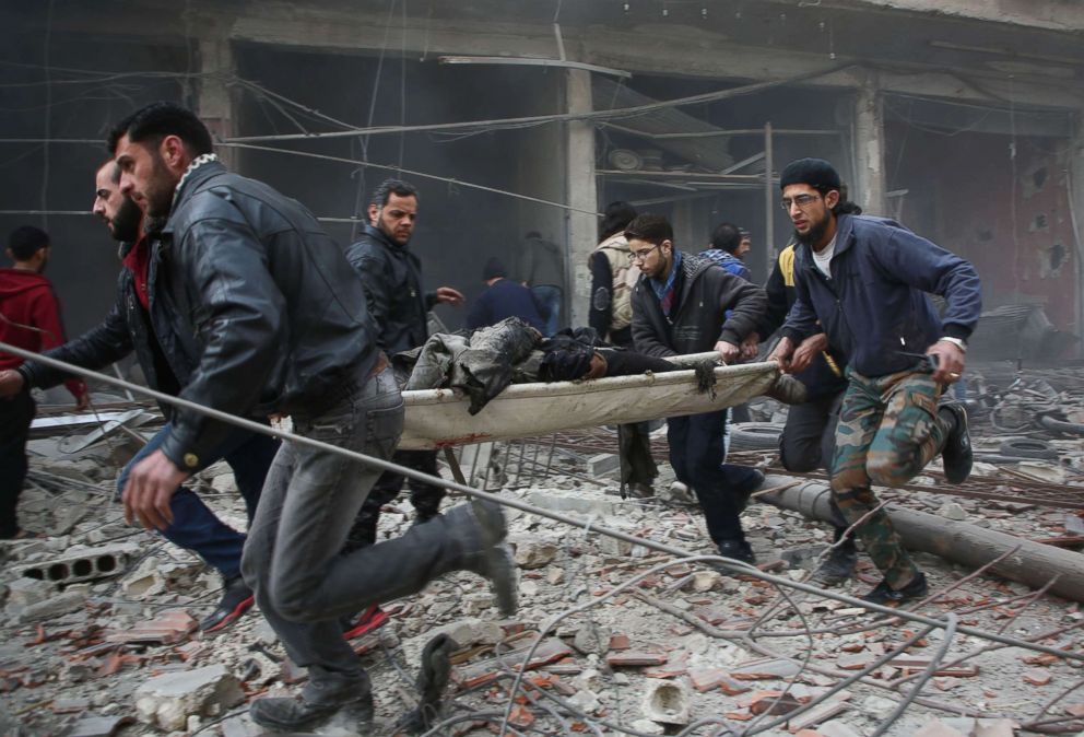 PHOTO: Syrians evacuate badly injured people following regime strikes on the besieged rebel-held enclave of Kafr Batna near Damascus, Feb. 6, 2018 where some 35 civilians were killed.