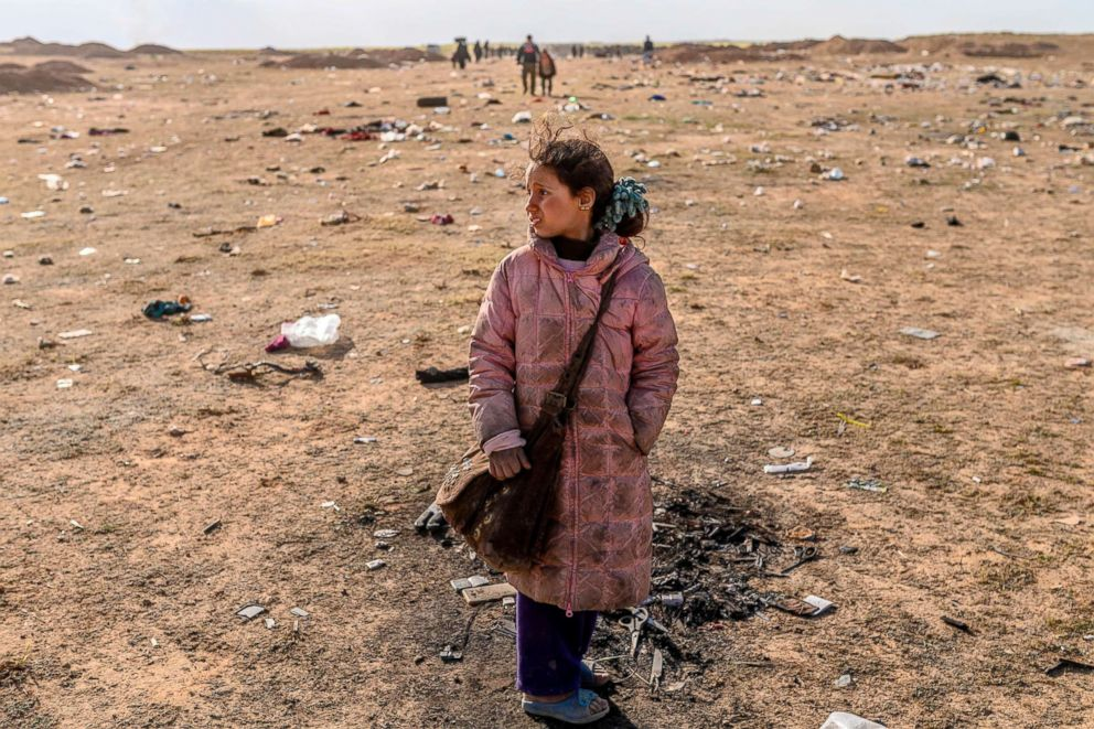 A girl stands alone as women and children evacuated from the Islamic State group's embattled holdout of Baghouz arrive at a screening area held by the U.S.-backed Kurdish-led Syrian Democratic Forces (SDF), in the eastern Syrian province of Deir Ezzor, March 5, 2019.