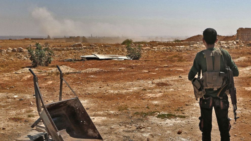 A Syrian rebel fighter watches smoke rising from an explosion in the northern countryside of the Idlib province, Sept. 5, 2018.