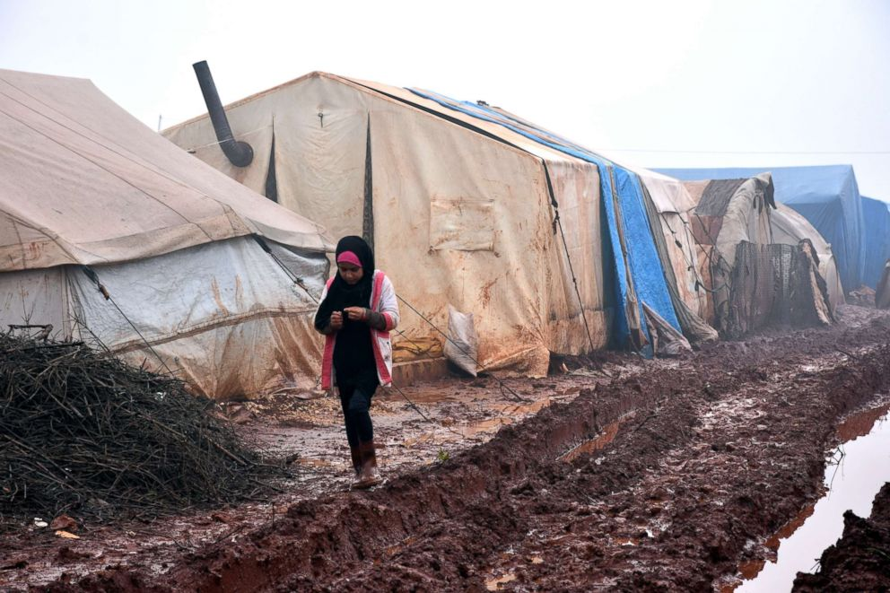 PHOTO: A child walks in the mud outside her shelter at Al-Ihsan refugee camp in Idlib, Syria, Jan. 15, 2019.