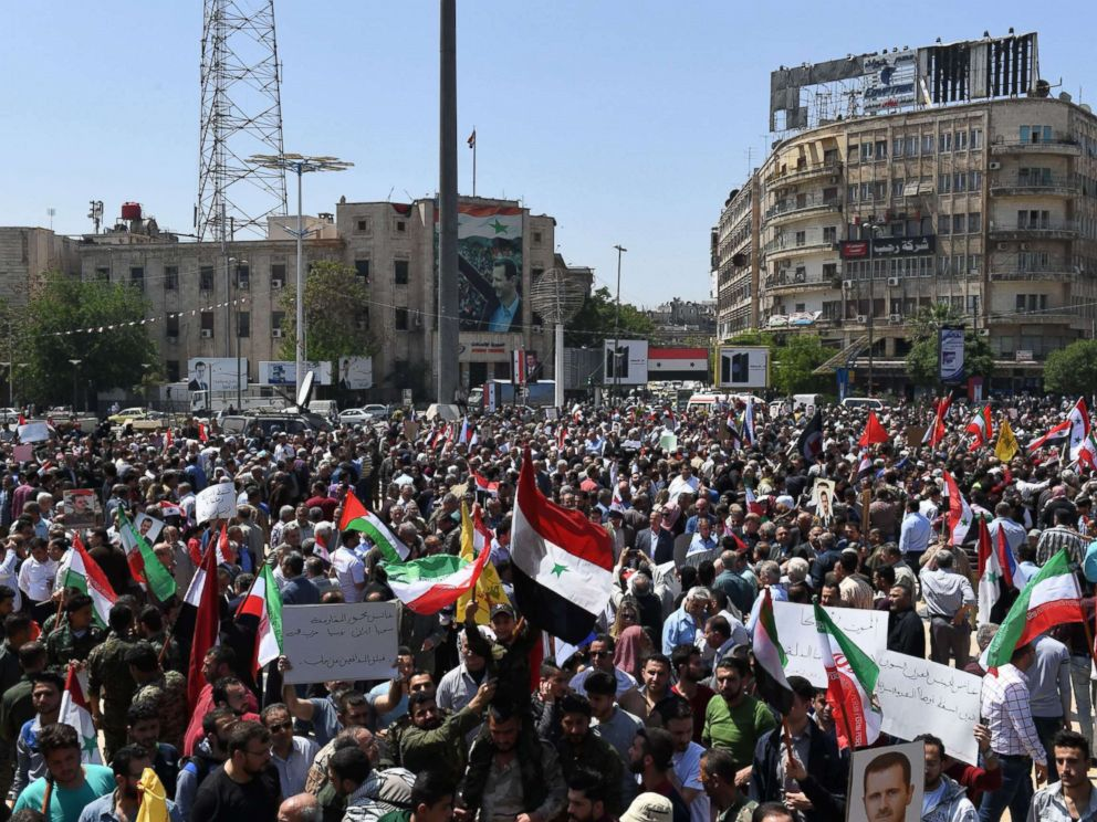 PHOTO: Syrians wave the national flag and portraits of President Bashar al-Assad as they gather in Aleppos Saadallah al-Jabiri square, April 14, 2018, to condemn the strikes carried out by the United States, Britain and France against the Syrian regime.