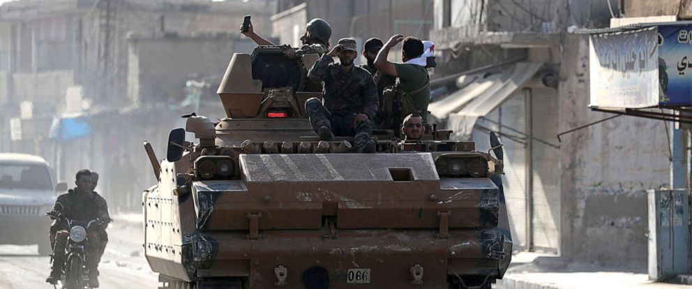 PHOTO: Turkey-backed Syrian rebel fighters are seen on a military vehicle in the town of Tal Abyad, Syria, Oct. 13, 2019.