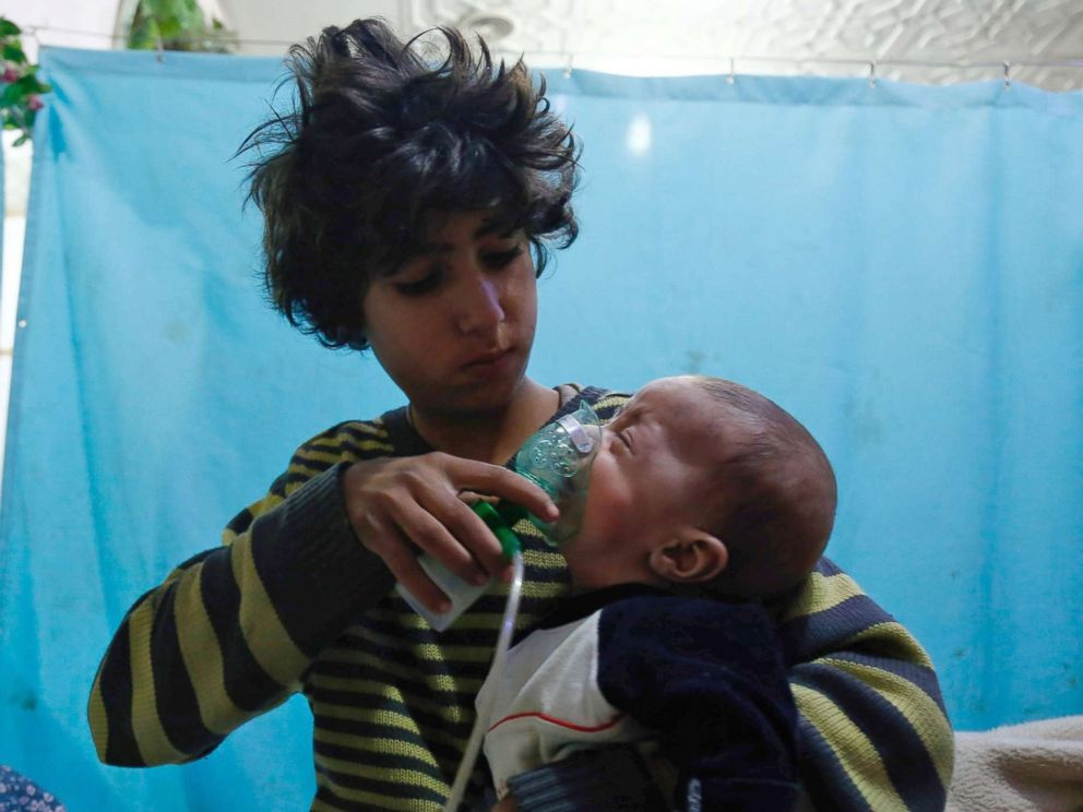 PHOTO: A Syrian boy holds an oxygen mask over the face of an infant at a makeshift hospital following a reported gas attack on the rebel-held besieged town of Douma in the eastern Ghouta region on the outskirts of the capital Damascus on Jan. 22, 2018.