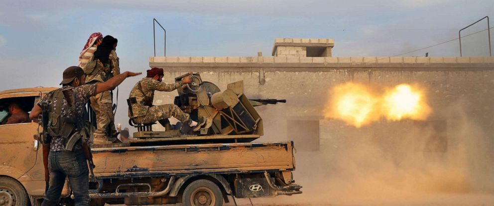 PHOTO: Turkey-backed Syrian opposition fighters fire a heavy machine-gun towards Kurdish fighters, in Syrias northern region of Manbij on Oct. 14, 2019.