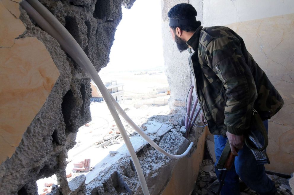 PHOTO: A Syrian rebel is looking of a window during government shelling on their position.