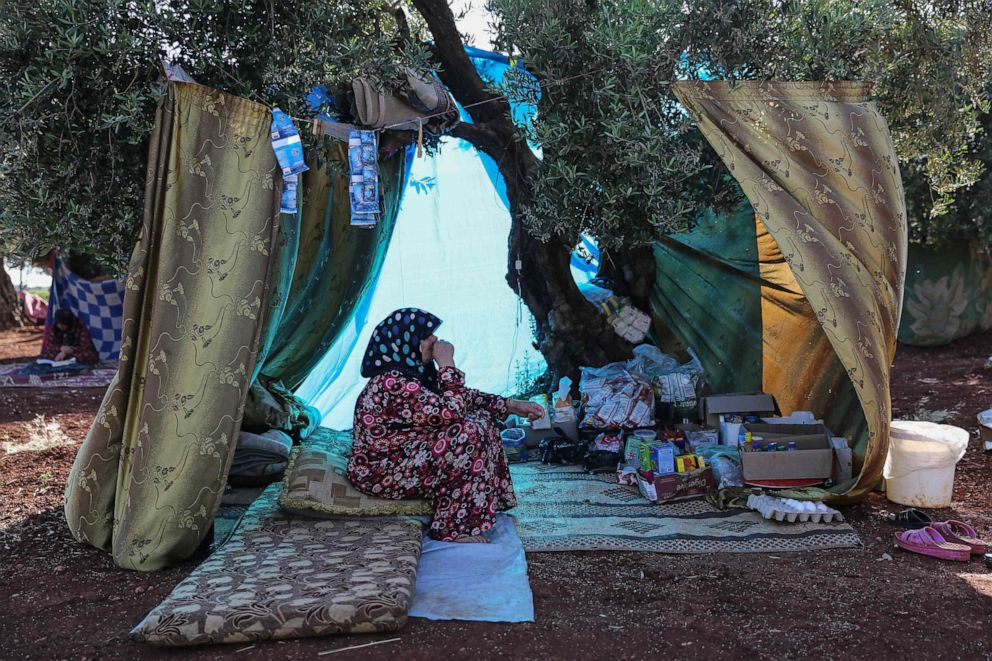 PHOTO: A displaced Syrian woman sits under the shade of a tree in a field near a camp for displaced people in the village of Atme, May 19, 2019.