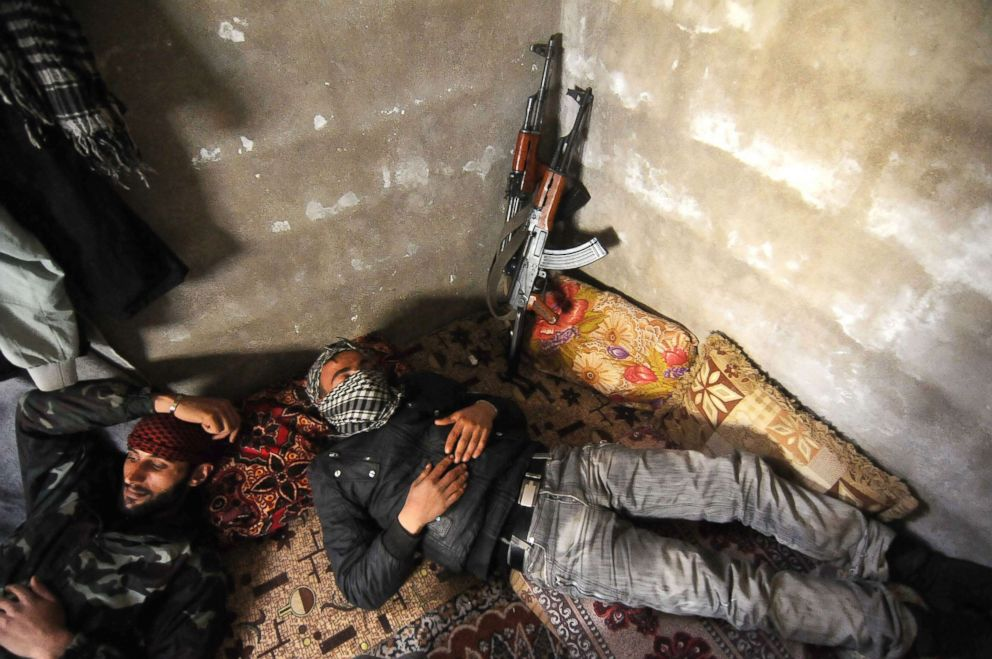 PHOTO: Three Syrian rebels are resting inside bunkers during a lull in the fighting.