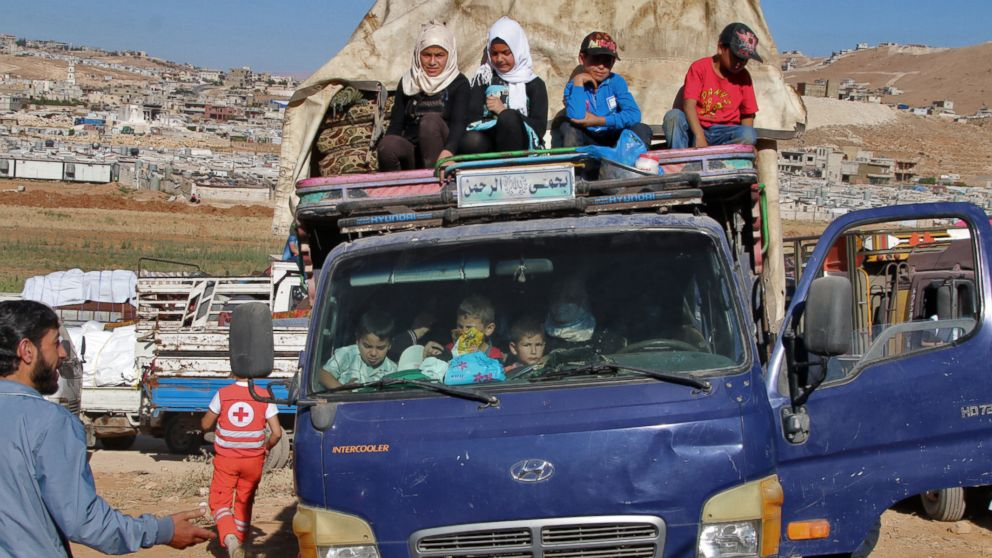 Syrian refugees ride a truck carrying their personal belongings at a Lebanese army checkpoint in Wadi Hmeid in the Bekaa valley, after leaving the village of Arsal to return to their homes in Syria's Qalamoun region on July 23, 2018.