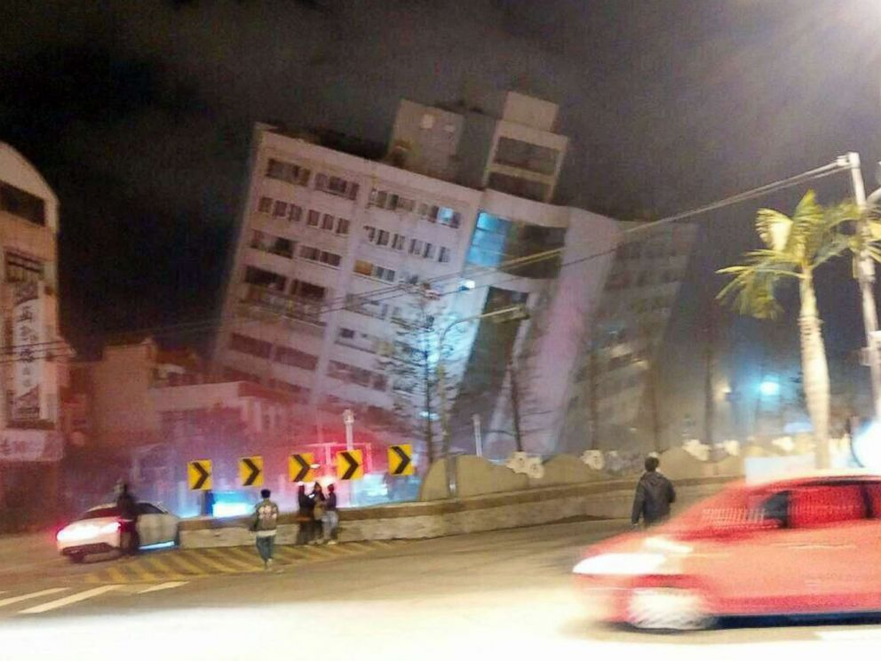 PHOTO: In this photo released by Hualien County Fire Bureau, rescuers are seen entering an building that collapsed onto its side from an early morning earthquake in Hualien County, eastern Taiwan, Feb. 7 2018.