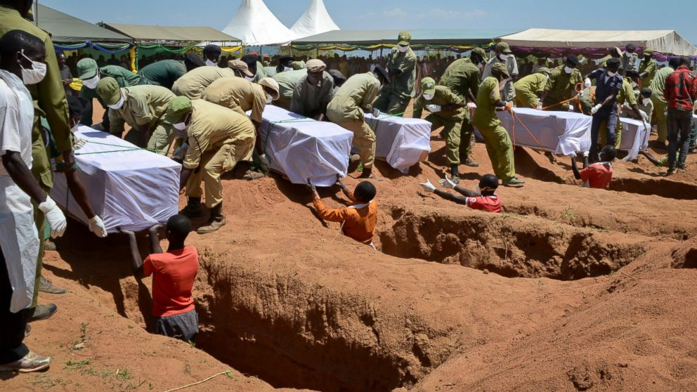 Coffins of some of the victims of the MV Nyerere passenger ferry capsizing are laid into graves during a mass burial ceremony on Ukara Island, Tanzania, Sunday, Sept. 23, 2018.