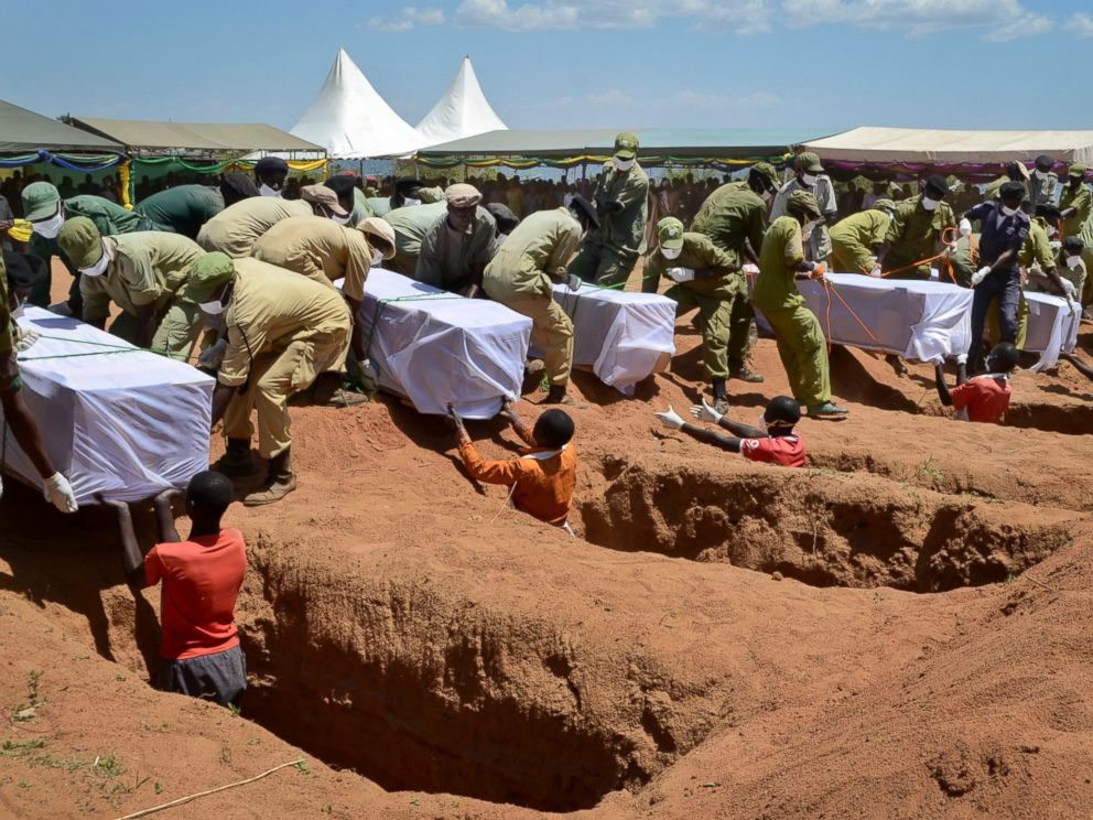 PHOTO: Coffins of some of the victims of the MV Nyerere passenger ferry capsizing are laid into graves during a mass burial ceremony on Ukara Island, Tanzania, Sunday, Sept. 23, 2018.