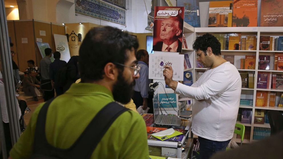 "A poster advertising the farsi translation of the book, ""Fire and Fury,"" by Michael Wolff. is displayed at a booth at the International Book Fair, in Tehran, Iran, Tuesday, May. 8, 2018."