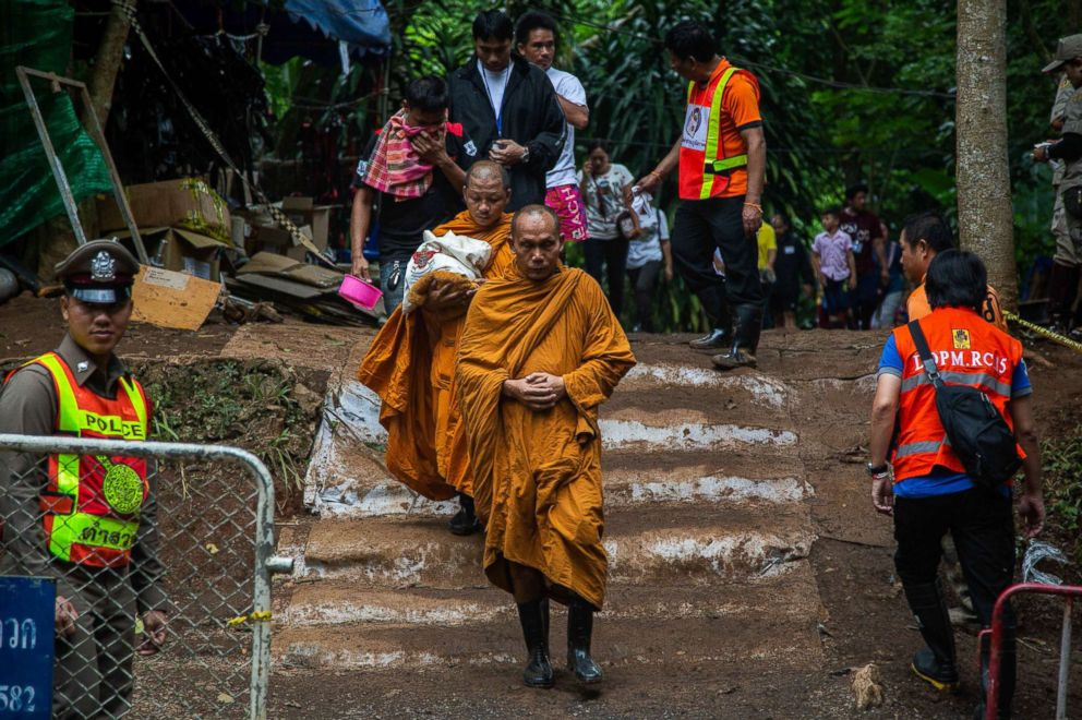 PHOTO: Monks lead out family members of the boys from the cave site after a morning prayer on July 7, 2018 in Chiang Rai, Thailand.