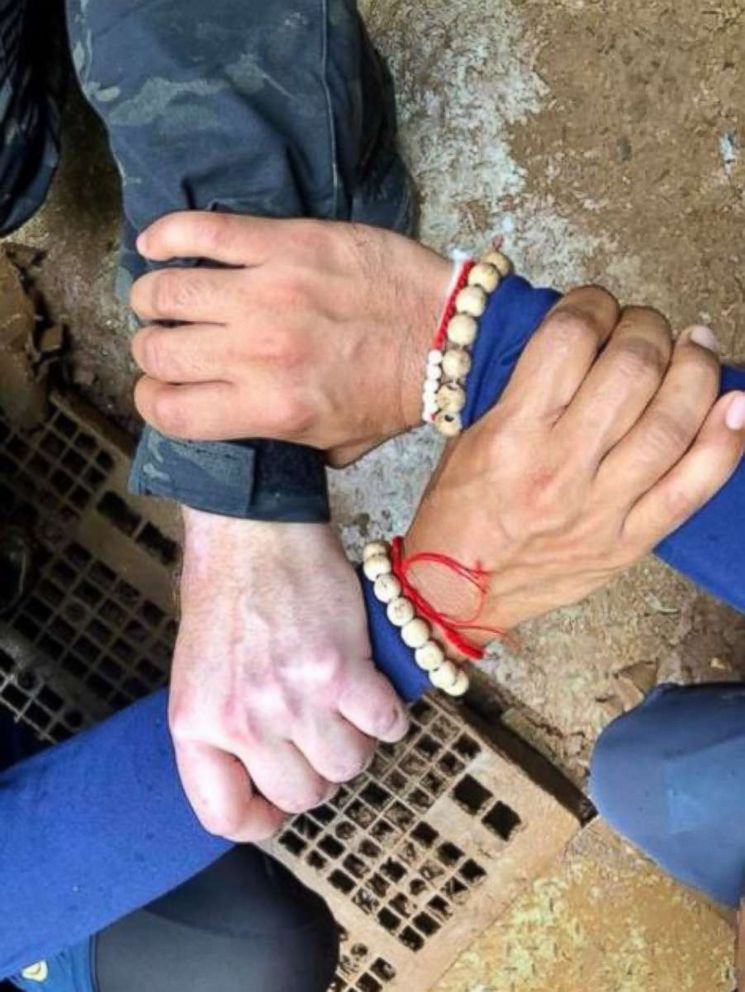 Rescuers in Thailand posted a photo of Thai and international divers linking hands before embarking on the rescue mission to save 12 boys and their soccer coach stuck in a cave, Sunday, July 8, 2018.