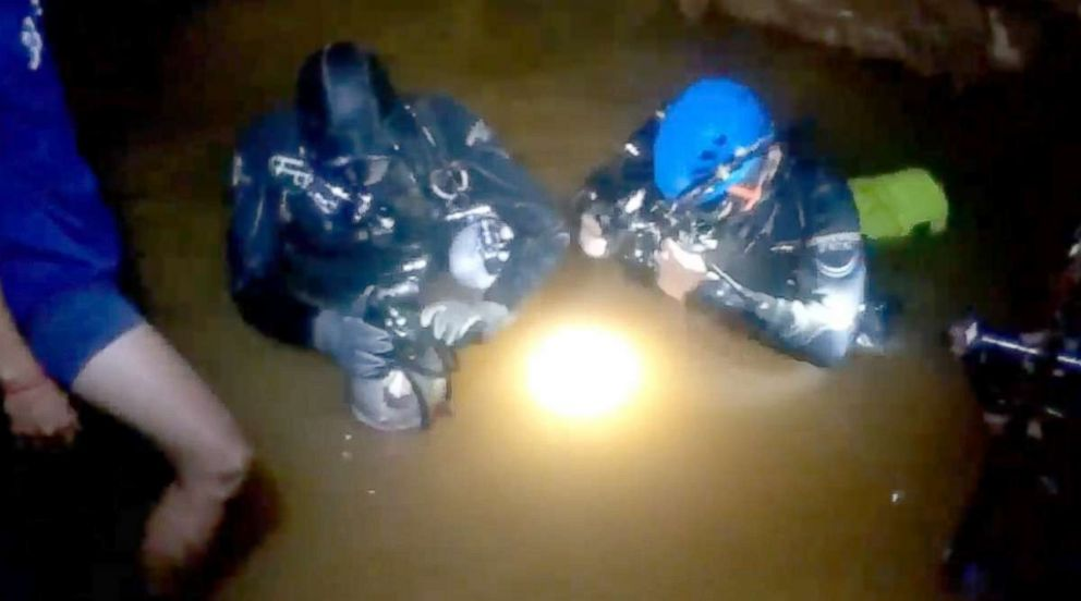 Two divers prepare their masks and air-tank regulators as they gear up for the scuba mission through the narrow flooded passageway leading to the cavern where each of the 12 boys and their coach – strapped into flexible stretchers and fitted with wetsuits and breathing apparatus – will be brought back through.