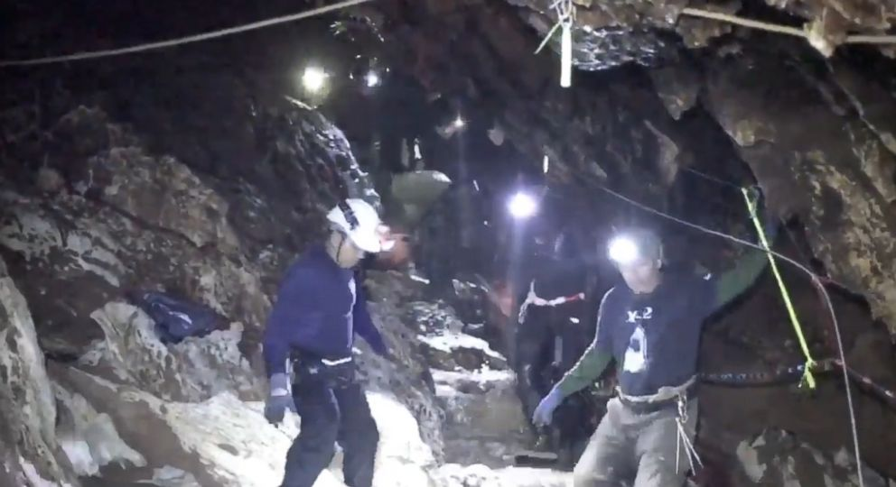 Rescuers carry one of the boys on a stretcher through a narrow steep passage in the cave as they trudge their way to safety.