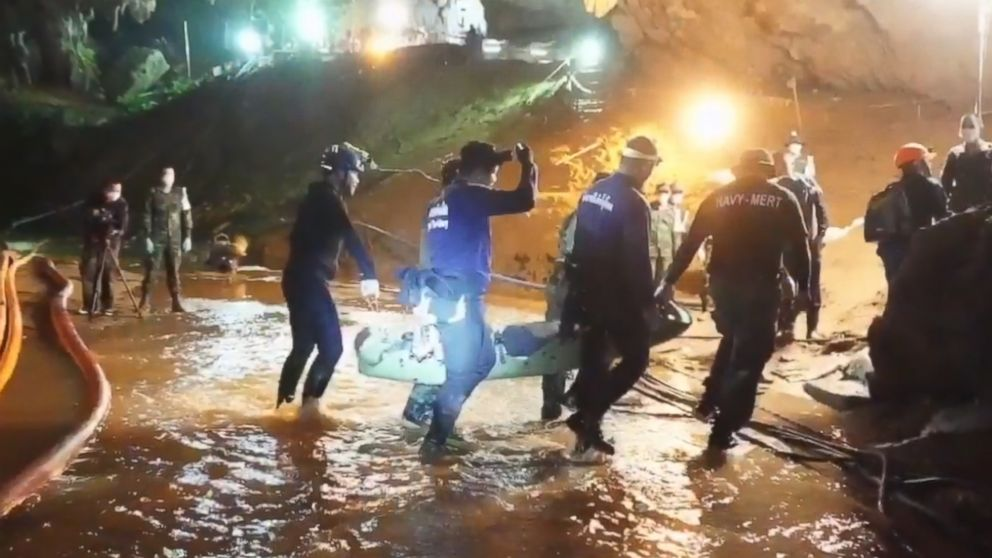 One of the rescued boys is carried by six rescuers across ankle-high stream of water to medics inside the cave for immediate treatment.