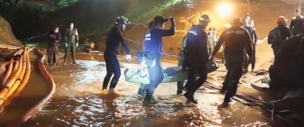 PHOTO: One of the rescued boys is carried by six rescuers across ankle-high stream of water to medics inside the cave for immediate treatment.
