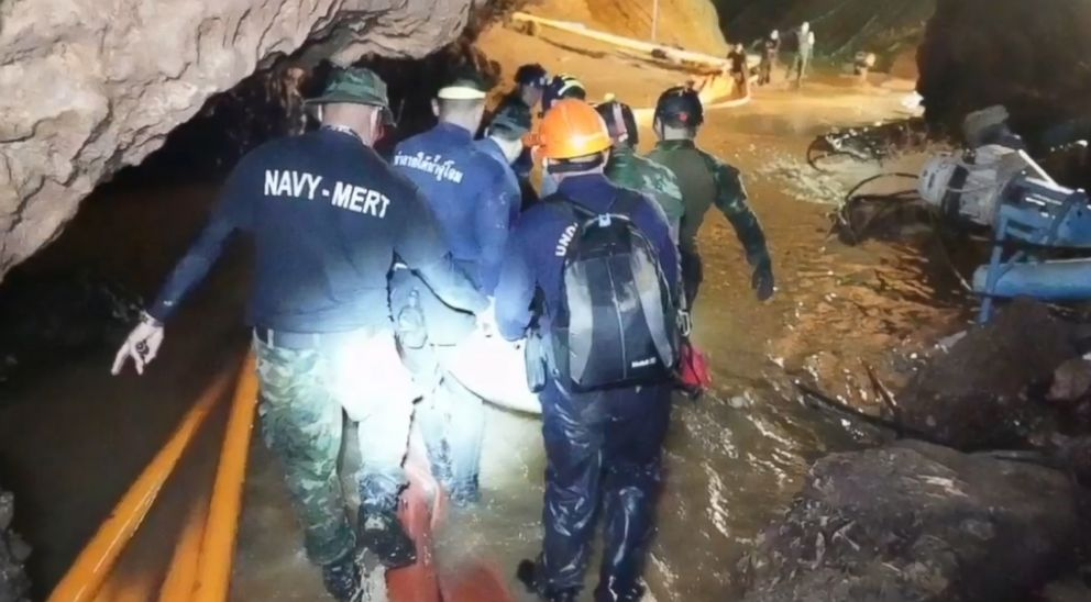A group of rescuers tote a stretcher containing one of the boys through a muddy and watery stretch as they head to the mouth of the cave on foot.