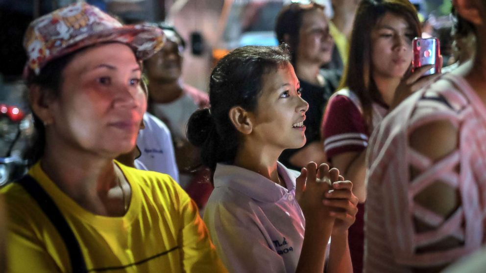 Onlookers at the junction in front of Chiangrai Prachanukroh Hospital watch and cheer as ambulances transport the last rescued schoolboys and their coach, July 10, 2018, in Chiang Rai, Thailand.