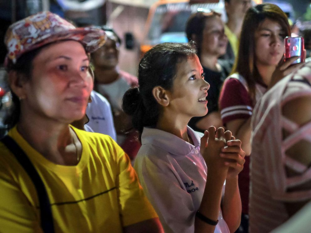 PHOTO: Onlookers at the junction in front of Chiangrai Prachanukroh Hospital watch and cheer as ambulances transport the last rescued schoolboys and their coach, July 10, 2018, in Chiang Rai, Thailand.
