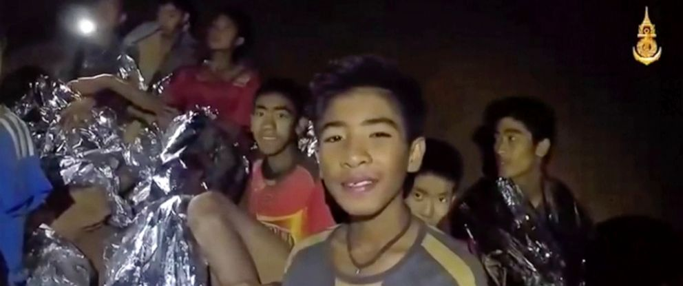 PHOTO: In this July 3, 2018, image taken from video provided by the Royal Thai Navy Facebook Page, Thai boys smile as Thai Navy Seal medic help injured children inside a cave in Mae Sai, northern Thailand.