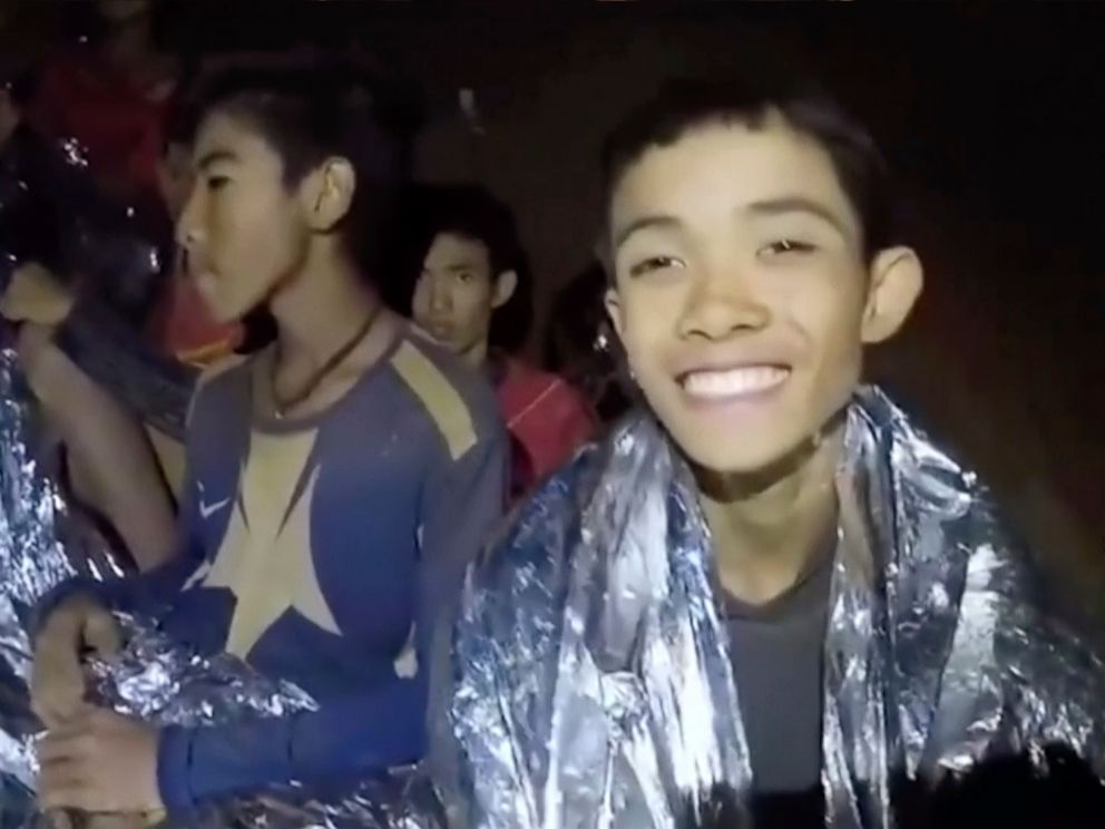 PHOTO: In this July 3, 2018, image taken from video provided by the Royal Thai Navy Facebook Page, a Thai boy smiles as Thai Navy SEAL medic help injured children inside a cave in Mae Sai, northern Thailand.