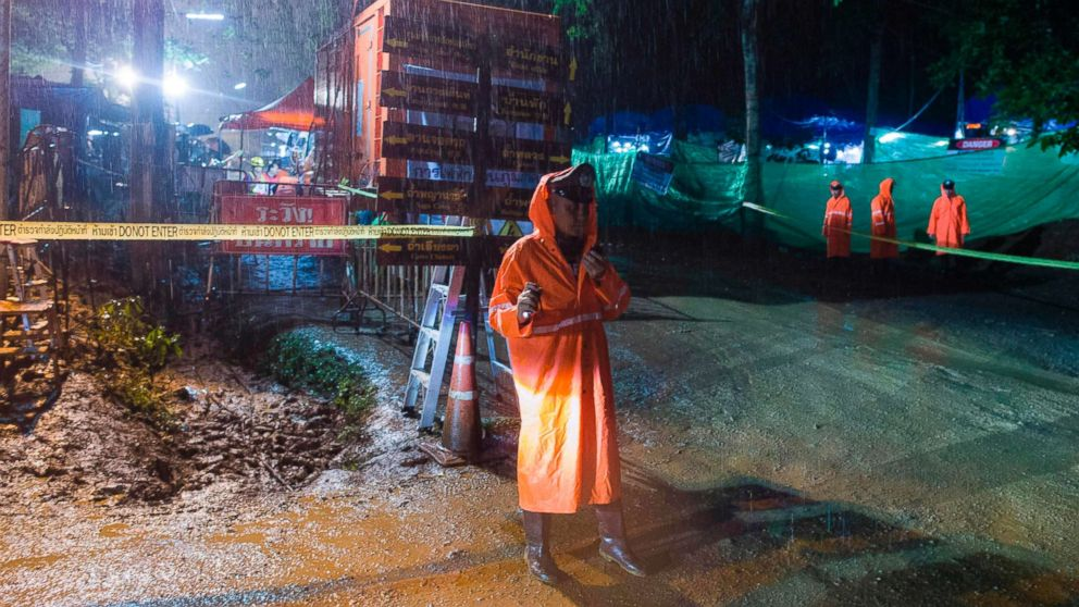 A Thai policeman guards an area under rainfall near the Tham Luang cave at the Khun Nam Nang Non Forest Park in Mae Sai district of Chiang Rai province, July 7, 2018, as rescue operation continues for the 12 boys and their football team coach.