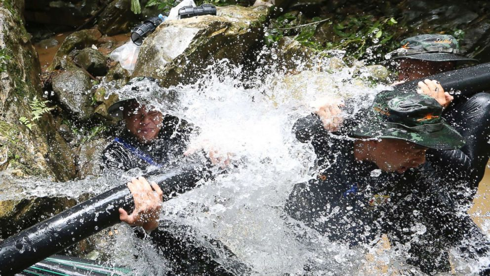Thai soldiers try to connect water pipes that will help bypass water from entering a cave where 12 boys and their soccer coach have been trapped since June 23, in Mae Sai, Chiang Rai province, in northern Thailand, July 7, 2018. Thai authorities are racing to pump out water from the flooded cave before more rains are forecast to hit the northern region.
