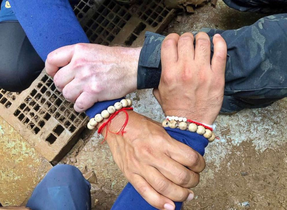 PHOTO: This undated photo released via the Thailand Navy SEAL Facebook page on July 8, 2018 shows rescuers hands locked with a caption reading We Thai and the international teams join forces to bring the young Wild Boars home.