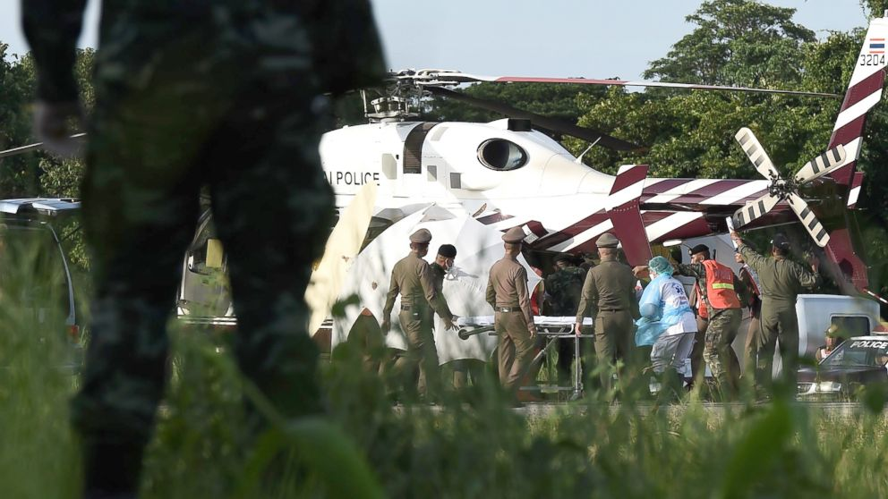 Rescue workers bring a stretcher close to a police helicopter at a military airport in Chiang Rai on July 9, 2018, as rescue operations continue for those still trapped inside the cave in Khun Nam Nang Non Forest Park in the Mae Sai district.