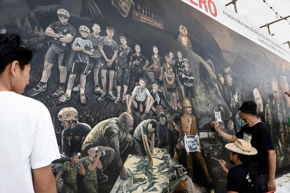 "Local artists work on a mural dedicated to the successful rescue of the 'Wild Boars"" football team outside an art gallery in Chiang Rai province, July 18, 2018, as family members await for the children's homecoming."