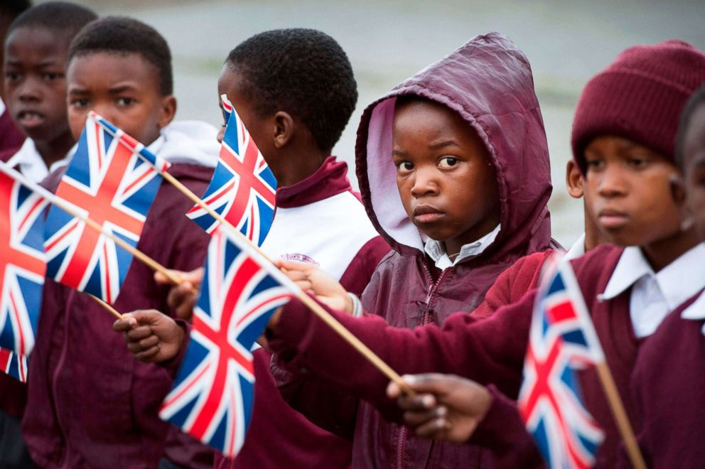 PHOTO: Schoolchildren hold British flags upon the arrival of the Britains Prime Minister at ID Mkhize Secondary School in Gugulethu township, Aug. 28, 2018.