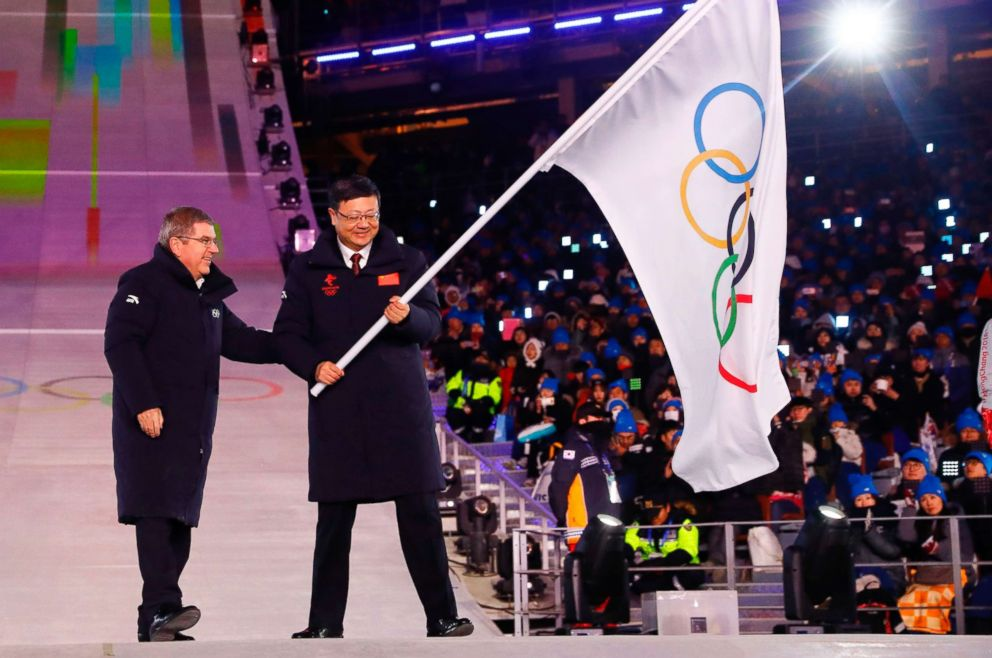PHOTO: The President of the International Olympic Committee Thomas Bach (L) passes on the pole during the handover ceremony of the Olympic flag to the Mayor of Beijing Chen Jining at the Pyeongchang Stadium, Feb. 25, 2018 in South Korea.