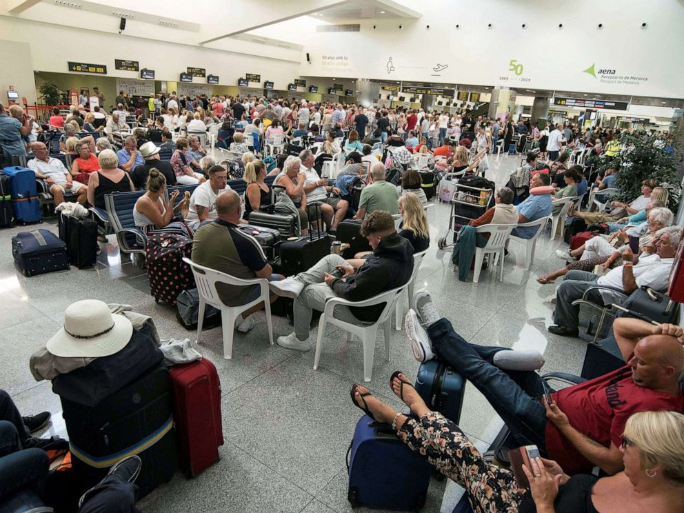 PHOTO: Several passengers wait at the airport in Menorca island, eastern Spain, Sept.23, 2019.