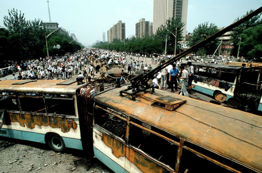 People look at buses and Chinese Army trucks and vehicles that were damaged or destroyed during the night of violence in and around Tiananmen Square, Beijing, June 04, 1989.