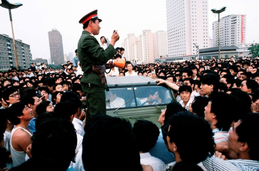 An officer talks with a crowd of pro-democracy demonstrators who are preventing his convoy of trucks filled with soldiers from entering Tiananmen Square, Beijing, June 01, 1989.