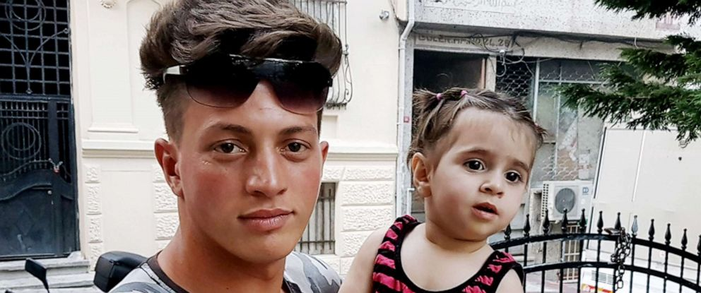 PHOTO: Algerian citizen Feuzi Zabaat poses with Syrian toddler Doha Muhammed he caught as she was falling from the second floor at Fatih district in Istanbul on June 27, 2019.
