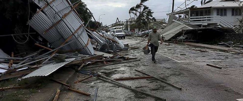 PHOTO: A resident of Nukualofa, the captial of Tonga, makes his way through the damage and devastation after cyclone Gita hit the island.