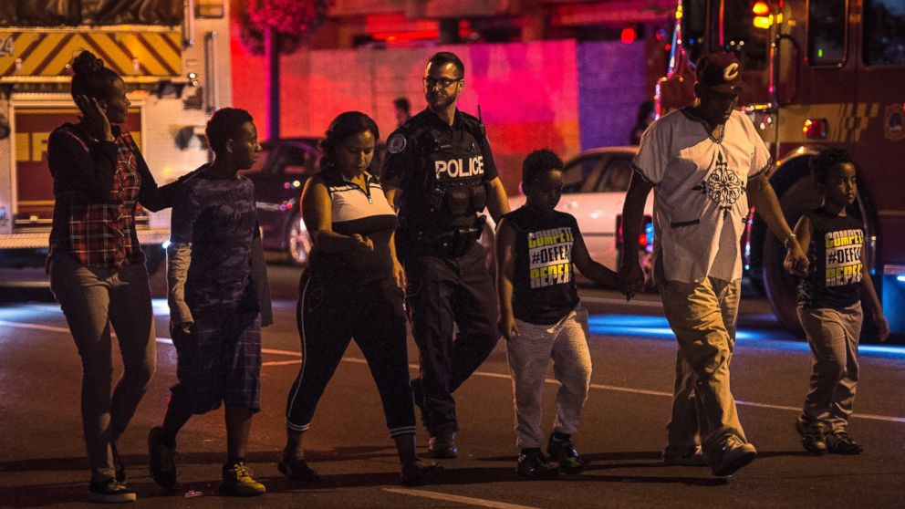 Police escort civilians away from the scene of a shooting, Sunday, July 22, 2018, in Toronto.