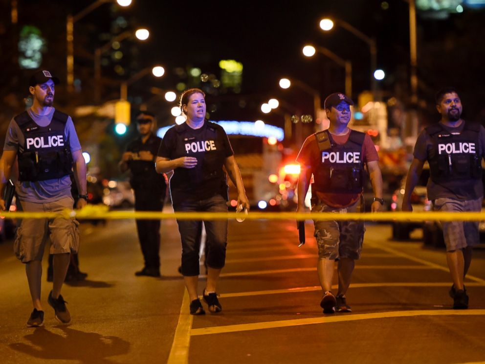 Plainclothes police officers work the scene of shooting in Toronto on Sunday, July 22, 2018.