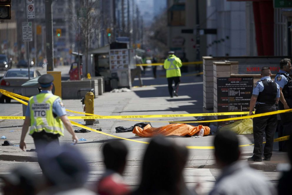 PHOTO: A tarp lays on top of a body on Yonge St. at Finch Ave. after a van plowed into pedestrians, April 23, 2018, in Toronto, Canada.