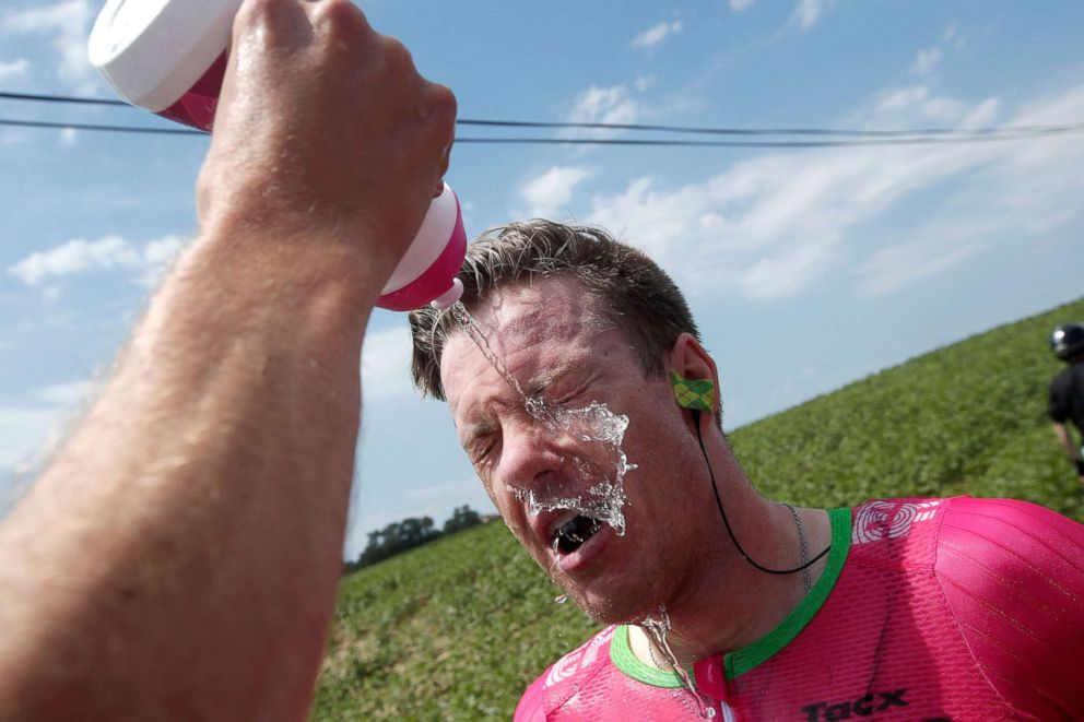 PHOTO: Simon Clarke of Australia cleans his eyes after tear gas was used by policemen against the farmers who protested during the Tour de France cycling race between Carcassonne and Bagneres-de-Luchon, France, July 24, 2018.